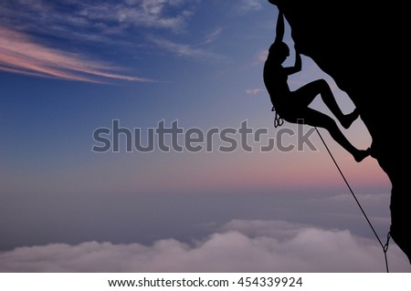 Silhouette of young woman lead climbing on overhanging cliff high above clouds and mountains, sun, beautiful colorful sky and clouds behind. Climber on top rope, hanging on rock.