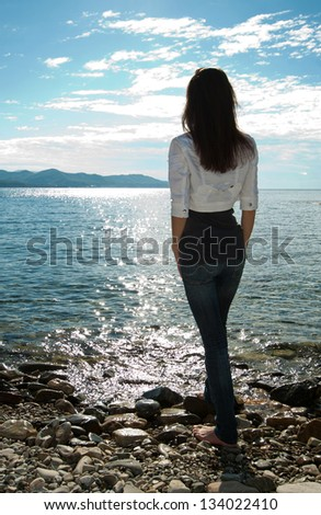 Silhouette of young woman looking at the sea, rear view - stock photo