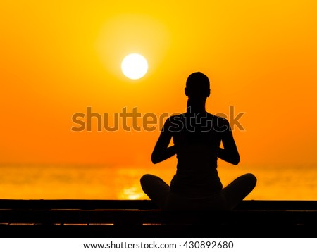 Silhouette of young woman practicing yoga in beautiful sunrise - stock photo