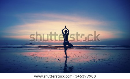 Silhouette of young woman practicing yoga on the beach at amazing sunset. - stock photo