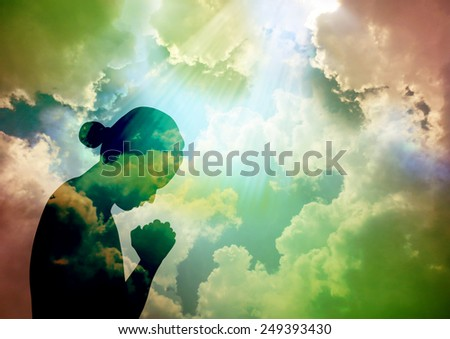 Silhouette of young woman praying to God - stock photo