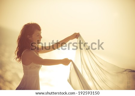 Silhouette of young woman relaxing at the beach. Summer vacation concept - stock photo