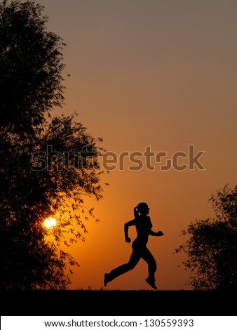 Silhouette of young woman running at summer sunset in the nature.