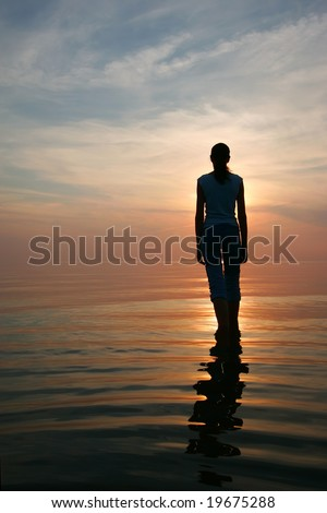 Silhouette of young woman standing in a water
