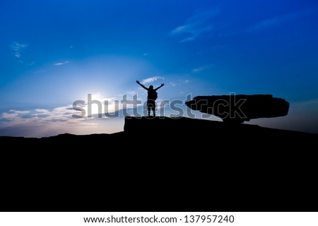 Silhouette of young woman standing over the rock on blue sky background