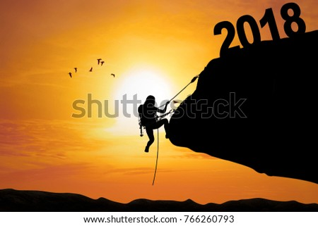 Silhouette of young woman using a rope for climbs cliff with numbers 2018. Shot at sunset time