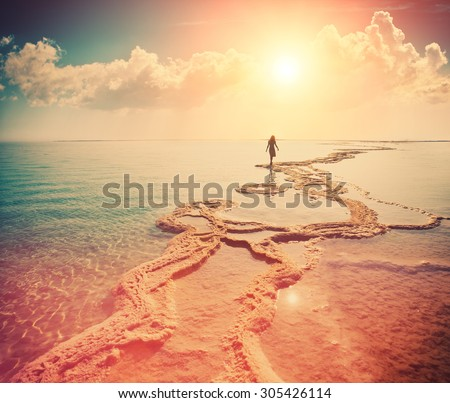 Silhouette of young woman walking on Dead Sea at sunrise - stock photo