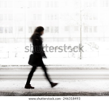 Silhouette of young woman walking on road in winter