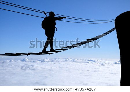 Silhouette of young woman walking to the cliff on the via ferrata bridge high above clouds and mountains, sun, beautiful colorful sky and clouds behind. Climber on via ferrata bridge.