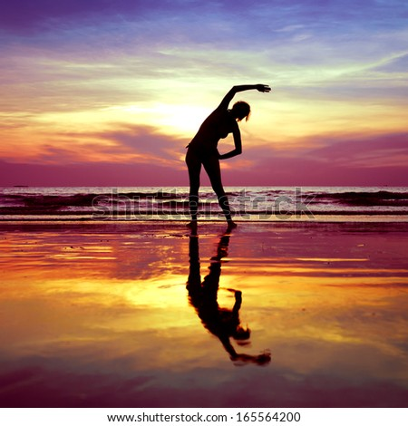 Silhouette of young woman, yoga stretching exercises on the beach at sunset - stock photo