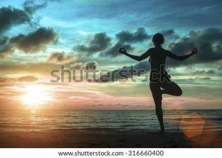 Silhouette of young women standing at yoga pose on the beach during an amazing surreal sunset.