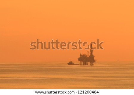 Silhouette Offshore Jack Up Drilling Rig and Boat At Sun Set Time (Yellow Tone)