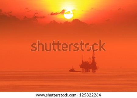Silhouette Offshore Jack Up Drilling Rig and Boat At Sun Set Time (Yellow Tone) - stock photo