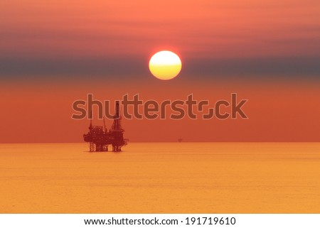 Silhouette Offshore Jack Up Drilling Rig At Sun Set Time (Yellow Tone) - stock photo