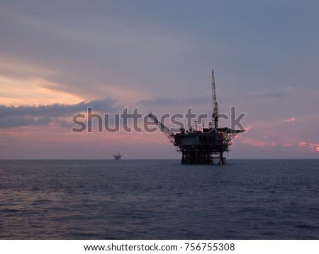 silhouette offshore platform with crane stand by for lifting personnel basket for shift change in the morning