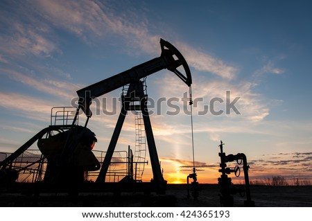 Silhouette oil pump jacks at sunset sky background.