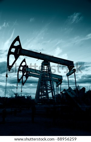 Silhouette oil pumps group on a sunset sky background. Toned. - stock photo