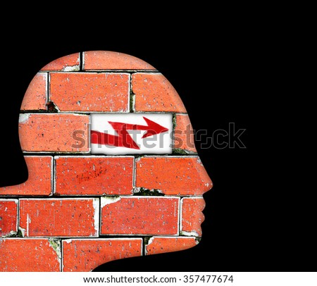 Silhouette outline of a man's head with a hole in a brick-wall with red arrow symbol  for the concept of mental illness.  - stock photo