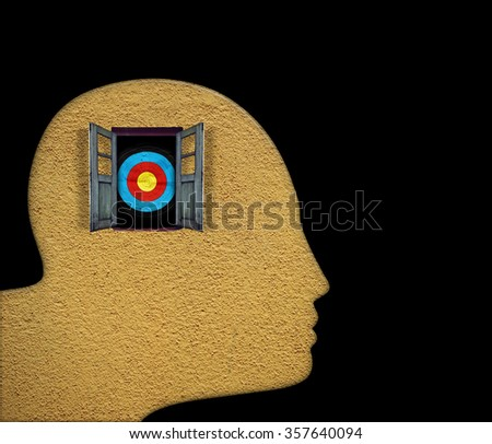 Silhouette outline of a man's head with a window in a mason wall with bulls eye target for the concept of targeting mental illness.  - stock photo