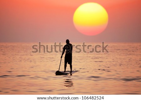Silhouette paddle board surfer on the sunset background - stock photo