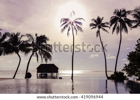 Silhouette palm tree on the beach and sea around beautiful luxury swimming pool and Water Villas (Bungalows)  in sunset , Maldives - stock photo