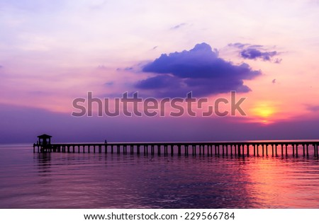 silhouette people driving bicycle on wood bridge with sunset - stock photo