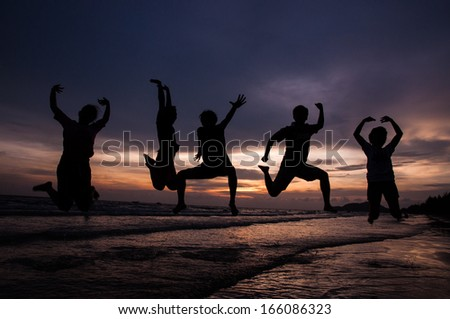 Silhouette people is jumping to enjoy the beach