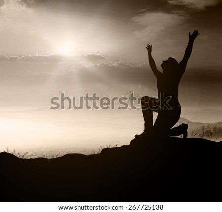 Silhouette people kneeling and raising hands over nature background. - stock photo