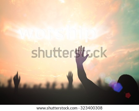 Silhouette people raising hands over blurred text for WORSHIP on beautiful nature background. Good Friday, Easter Sunday, Holy Week, He is risen concept. - stock photo