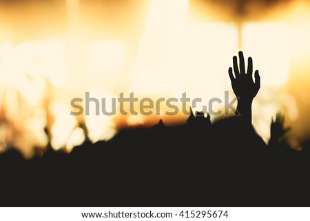 Silhouette people raising hands over blurred the cross on beautiful golden autumn sky sunset background. Forgive Mercy Humble Hallelujah Thankful Redeemer Amen Pray Hope Way Hosanna Give God concept. - stock photo
