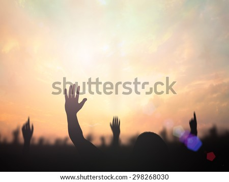 Silhouette people raising hands over blurred the cross on beautiful golden autumn sunset background. Worship, Forgiveness, Mercy, Humble, Evangelical, Hallelujah, Adoration, Glorify, Redeemer concept. - stock photo