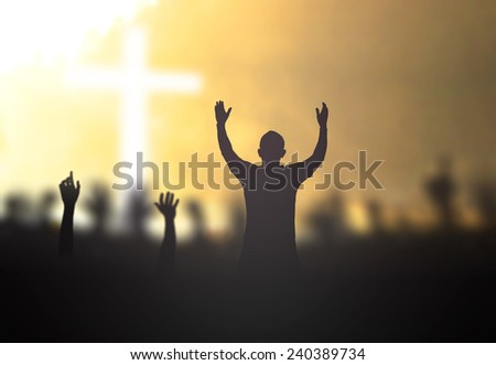 Silhouette people raising hands over blurred the cross on nature background. - stock photo