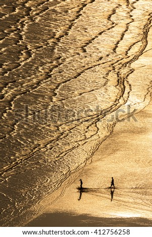 silhouette people walk on tropical Chao Laow  beach in Chanthaburi province east of Thailand with beautiful golden light in evening - stock photo