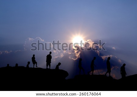 silhouette people walking across mountain view - stock photo
