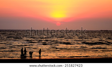 Silhouette people walking in sea with sunset sky, Bangsaen, Chonburi, Thailand