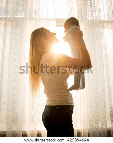 Silhouette photo against sun of cheerful young mother playing with baby at big window - stock photo