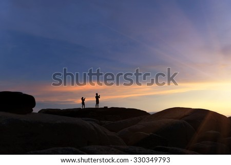 silhouette Photo Of Young couples take sunset With Mobile Phones.