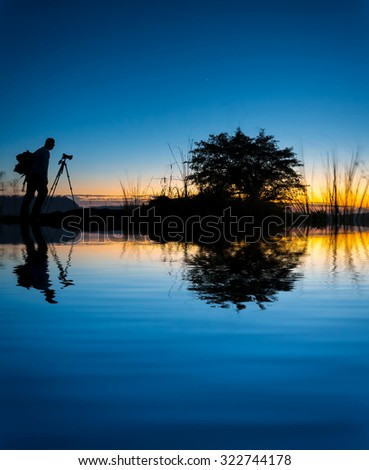 silhouette photographer water reflection on amazing color during sunrise - stock photo