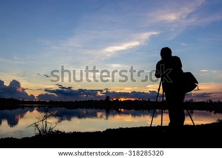 Silhouette photographer with sunset at lake background - stock photo