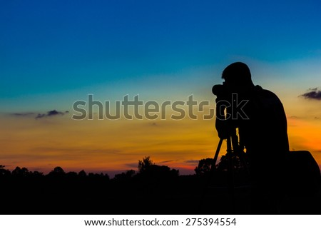 Silhouette photographer with sunset background - stock photo