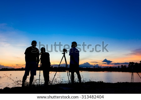 Silhouette photographers with sunset at lake background - stock photo