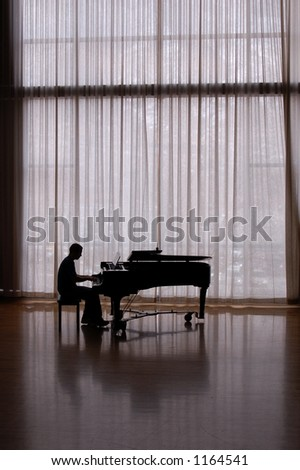 silhouette pianist in sunlit studio
