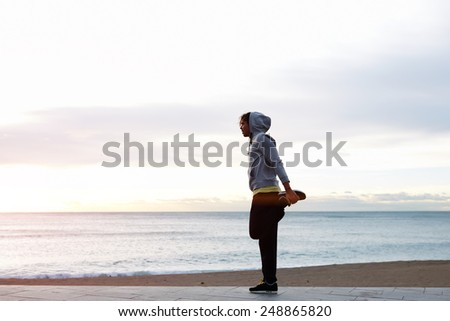Silhouette portrait of a man exercising on beach, out for a run on a early morning - stock photo