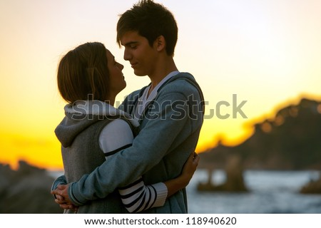 Silhouette portrait of young romantic couple at sunset. - stock photo