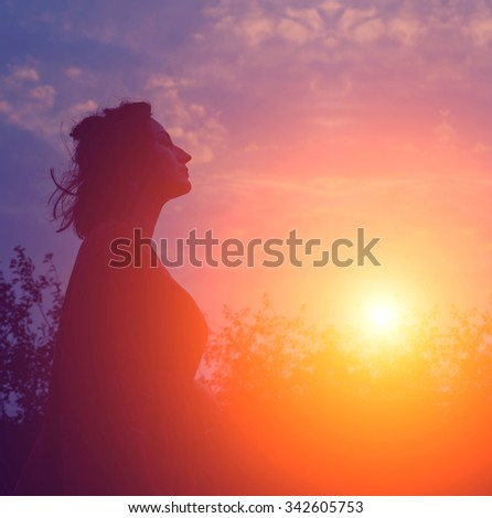 Silhouette portrait of young serious woman. Silhouette of a young woman relaxing on a beautiful sunset. Happy woman enjoying nature sunset. Freedom, happiness, enjoyment, concept of beautiful girl.