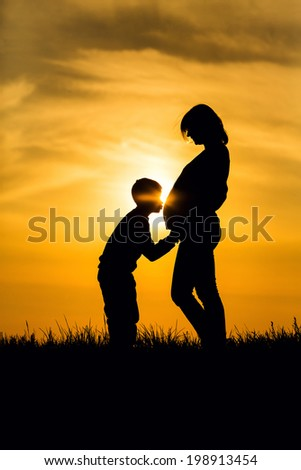 Silhouette pregnant woman and her son kissed