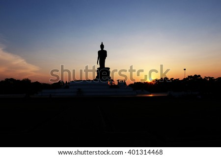 Silhouette public big white Buddha, over golden light sunset in Thailand background. Thailand travel concept. End of Buddhist Lent Day concept. - stock photo