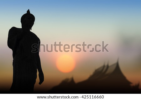 Silhouette public Buddha statue, over sunset in Thailand background.