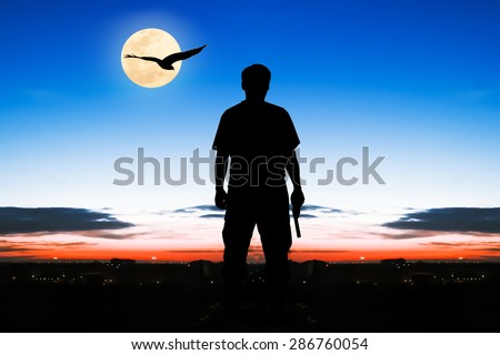 silhouette rear of man standing hand hold holding gun revolvers on sunrise and full moon eagle fly on the sky in the city background - stock photo