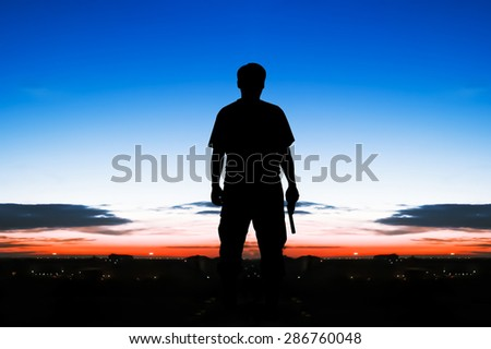 silhouette rear of man standing hand hold holding gun revolvers on sunrise in the city background - stock photo